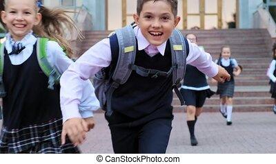 schoolboy in uniform and friends run along school yard - ...