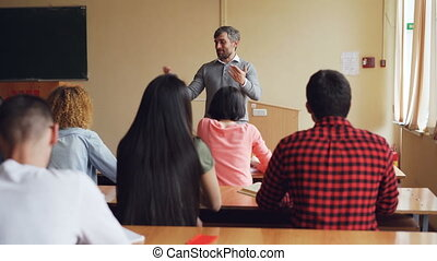 Schoolboy is raising hand and answering teacher's question while educator is checking knowledge standing in front of students' desk. Schools and people concept.