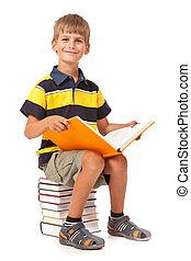 Schoolboy is sitting on books