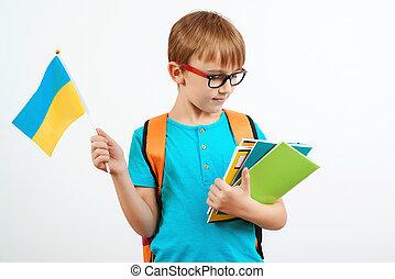 Schoolboy learning ukrainian language. Cute boy with backpack holding ukrainian flag.