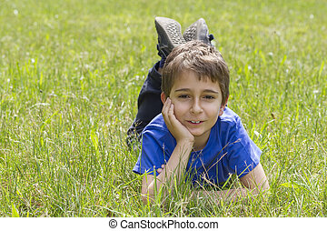 Schoolboy lies in the grass.