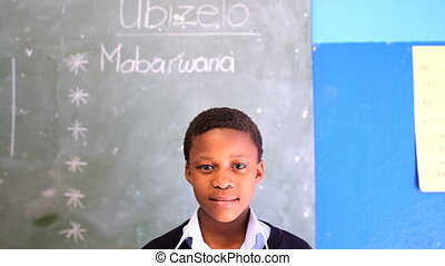 Smiling schoolboy looking at camera in classroom at school 4k