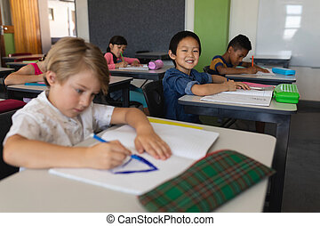Schoolboy looking at camera while studying in classroom