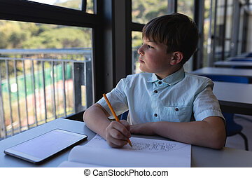 Schoolboy looking away while drawing on notebook at desk in classroom