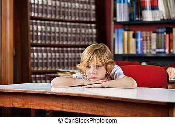 Schoolboy Looking Away While Leaning On Table