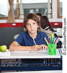 Schoolboy Looking Away While Writing At Desk