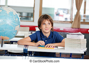Schoolboy Looking Away With Globe And Books At Desk