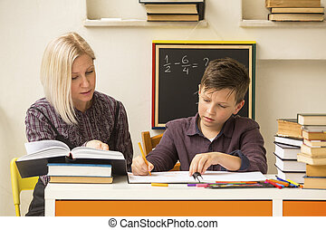 Schoolboy makes engaged homework with the tutor.