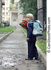 Schoolboy on his way to the school. Boy going to the first class in his school on the path. Children and education in the city.