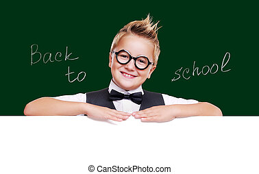 Schoolboy on school blackboard background