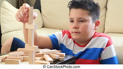 Schoolboy playing with wooden tower block game - Preteen boy...