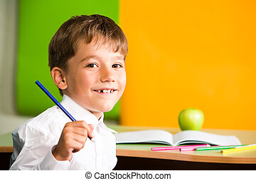 Portrait of handsome schoolboy holding pencil in hand and looking at camera