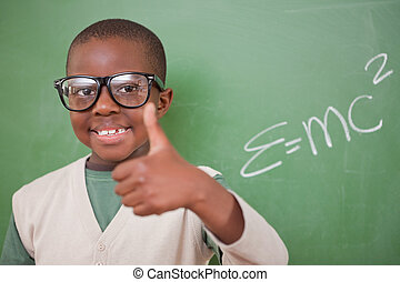 Schoolboy posing with the the mass-energy equivalence formula and the thumb up in front of a blackboard
