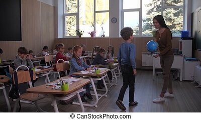 Curly active primary school student raising hand and going to teacher holding geographic globe. Clever elementary age schoolboy showing his knowledge of geography during lesson in junior school