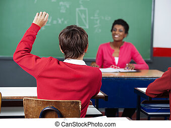 Schoolboy Raising Hand In Classroom