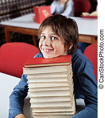 Schoolboy Resting Chin On Stacked Books At Table