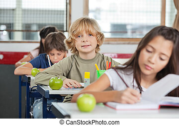 Schoolboy Sitting In A Row With Classmates At Classroom
