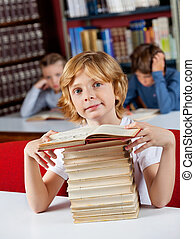 Schoolboy Sitting With Stack Of Books At Table In Library