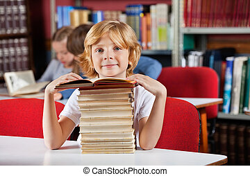 Schoolboy Sitting With Stack Of Books In Library