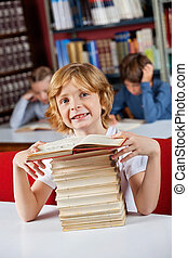 Schoolboy Smiling While Sitting With Stack Of Books In Library