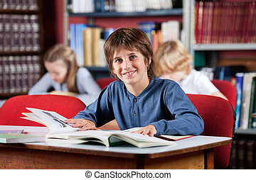 Schoolboy Smiling With Books At Table In Library