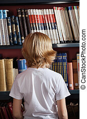 Schoolboy Standing Against Bookshelf In Library