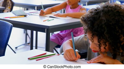 Front view of cute mixed race schoolboy studying at desk in classroom at school. Schoolkids doing their classwork 4k