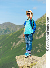 schoolboy traveler with a backpack high in the mountains on a rock