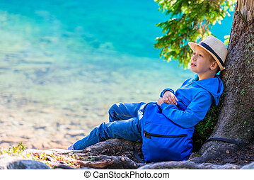 Schoolboy traveler with a rucksack resting by the lake in the Tatras