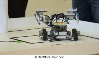 Schoolboy trialing his robot on path challenge - Close-up...