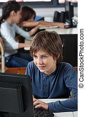 Schoolboy Using Computer At Desk