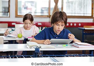 Schoolboy Using Digital Tablet In Classroom