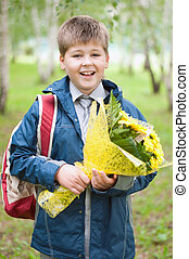 Schoolboy with a bouquet of yellow chrysanthemums in the park