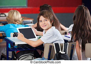 Schoolboy With Digital Tablet Sitting At Desk In Classroom