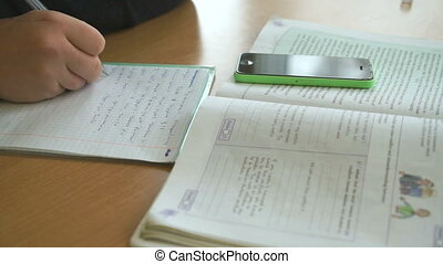 Schoolboy writes the text in notebook on lesson