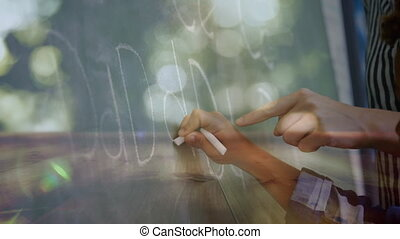 Animation of schoolboy writing with chalk on chalkboard, female teacher helping him at school in class. Global learning education school concept digitally generated image.