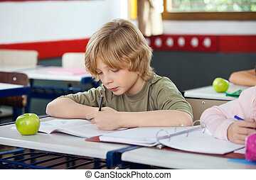Schoolboy Writing On Book In Classroom