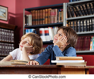 Schoolboys Looking Away While Sitting In Library