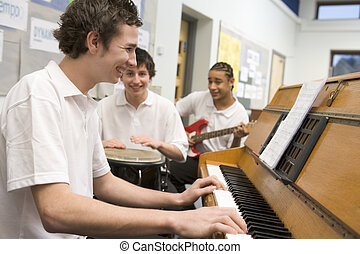 Schoolboys playing musical instruments in music class