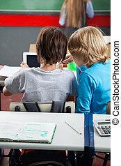 Schoolboys Using Digital Tablet At Desk