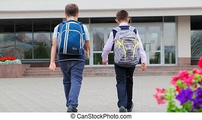 schoolboys with large backpacks walk to school building - ...