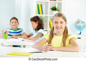 Schoolchild at desk - Lovely girl looking at camera with ...