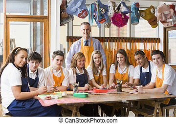 Schoolchildren and teacher sitting around a table in art class