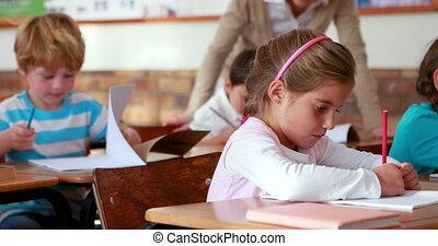 Schoolchildren colouring in books in classroom in elementary...