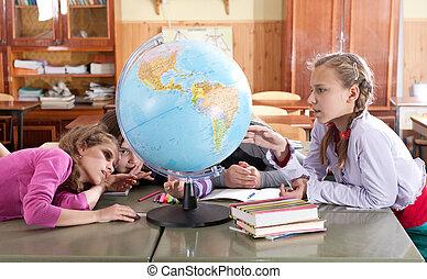 Schoolchildren exploring globe in classroom - Schoolchildren...