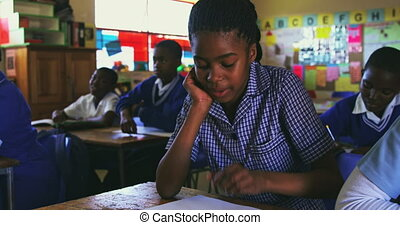 Front view close up of a young African schoolgirl writing in her notebook during a lesson in a township elementary school classroom, in the background her classmates are also writing in their books 4k