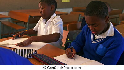 Front view close up of two young African schoolboys sitting at their desks writing during a lesson in a township elementary school classroom 4k