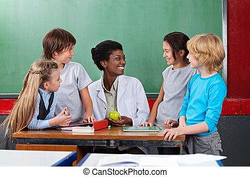 Schoolchildren Looking Teacher Sitting At Desk