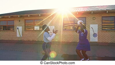 Slow motion side view of a group of young African schoolgirls and schoolboys jumping and playing with a ball in the playground at a township elementary school, backlit by sunlight 4k
