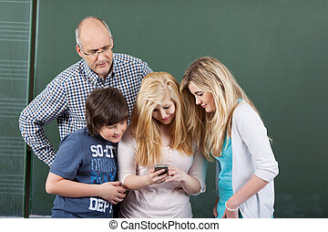 Schoolchildren playing with a mobile phone grouped together...